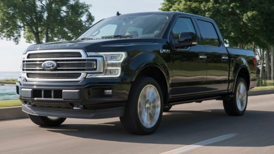 Image of a black 2019 Ford F-150 driving near a park.