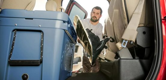 Image of a man loading cargo into the back of a Ford truck.